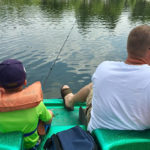 Father and Son in a paddle boat fishing on a lake, picture taken from behind them