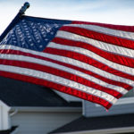 American flag flying in the wind with houses in the background