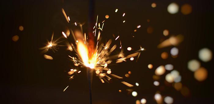 Bright sparkler throwing sparks on a dark background