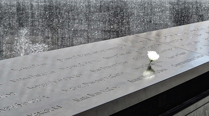 Photo of the names at the 9 11 memorial with a white rose on the national day of service and remembrance