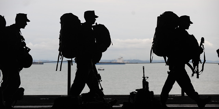 Servicemen and women in full gear silhouetted against the sky and sea